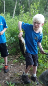 Mim holding a fish he caught at cub scout camp