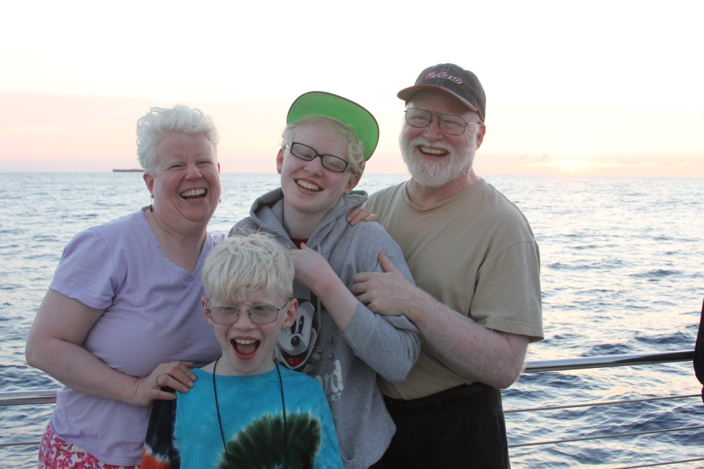 The four of us sharing a laugh in Hawaii. My husband and I and our two children are albinos. We all have the genetic condition albinism.